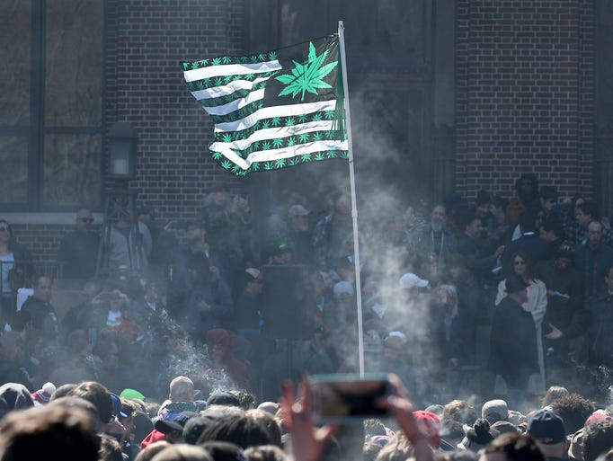 A marijuana flag flies high among a cloud of pot smoke
