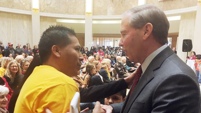 "Sen. Tom Udall, D-N.M, right, speaks to an immigrant rights advocate at the statehouse in Santa Fe, N.M., Monday, Feb. 6, 2017. Udall told advocates on Monday that President Donald Trump's travel ban on seven Muslim-majority countries is ""illegal and unconstitutional"" and vowed to fight it with other Democratic senators."