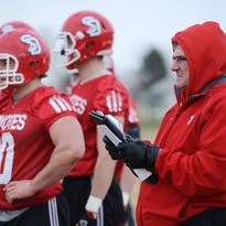 USD football coach Joe Glenn watches over a practice in late March. Glenn says a budget such as USD's for football recruiting means carefully targeting players who are a long distance from Vermillion.