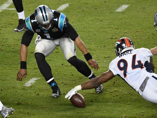 Denver Broncos outside linebacker DeMarcus Ware (94) grabs a loose ball ahead of Carolina Panthers quarterback Cam Newton (1) during the fourth quarter in Super Bowl 50 at Levi's Stadium.