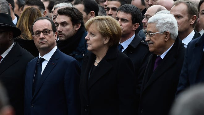 Francois Hollande, Angela Merkel and Mahmoud Abbas walk together during a unity rally in Paris on Sunday.