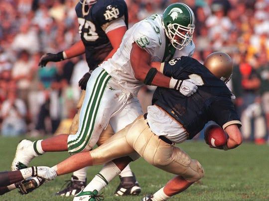 MSU's Dimitrius Underwood sacks Notre Dame quarterback Ron Powlus on Sat. 9/20/97.