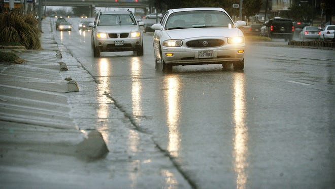 Motorists drive carefully through a rain storm in this file photo. The weather center is predicting rain and possibly snow for Thursday into Friday morning.