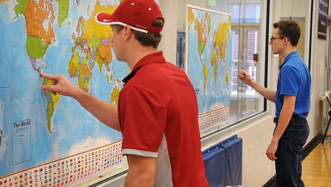 Josh Skipworth, left, and Aspen Brashear search for a random country called out during a geography game called Map Madness  at Wichita Christian School. The tournament mimics the March Madness college basketball tournament.