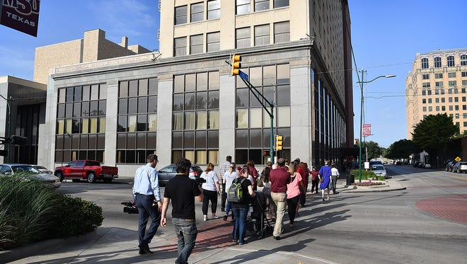 """in this file photo, attendees of a press conference in Park Central  walk across Scott Street to the City National Building where Texoma Community Credit Union announced a branch opening. M.B. Investigations will also call the City National Building """"home."""""""