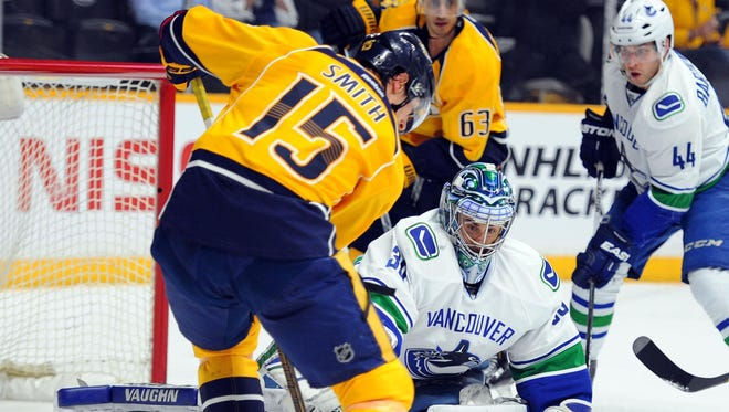 Canucks goalie Ryan Miller (30) battles for a loose puck with Predators center Craig Smith (15) in the first period Thursday.
