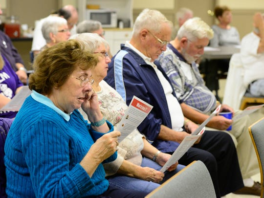 The crowd reads through literature handed out by State representative Bill Reineke on Issue 3 Monday night at the Fremont Baptist Temple.