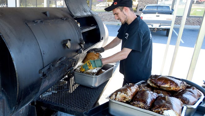 Pit master Dillon Lewis checks the Boston butts and removes those that are ready from the smoker outside Sooner BBQ in Stuarts Draft on Oct. 13, 2015.