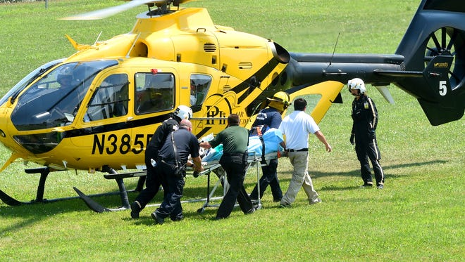 First responders transfer a 66-year-old man from rescue squad to a waiting PHI Air Medical's Aircare 5 helicopter on a ball field behind Verona Elementary on Thursday, July 21, 2016. The man became injured after he fell off a scaffolding next to a barn at 1609 Lee Highway in Fort Defiance.