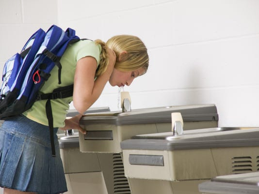 Student drinking from water fountain