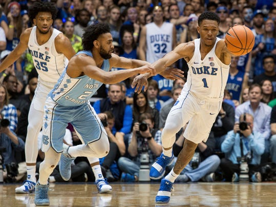 Duke's Trevon Duval (1) reaches for a loose ball ahead of North Carolina's Joel Berry II (2) during the first half of an NCAA college basketball game in Durham, N.C., Saturday, March 3, 2018. (AP Photo/Ben McKeown)