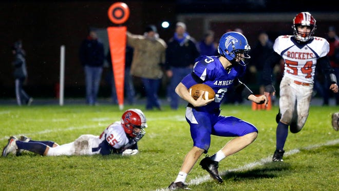 Amherst senior quarterback Marcus Glodowski evades opponents during a Division 5 second round playoff game with Spencer/Columbus Catholic on Friday night in Amherst.