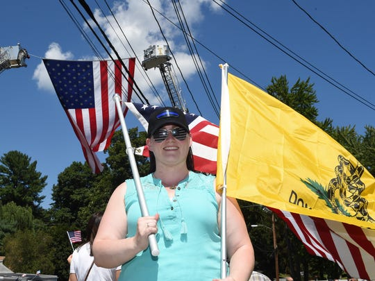 Robson Druta of Wappingers Falls carries flags during Saturday's rally at Arlington Fire District's Croft Corners Fire Company in the Town of Poughkeepsie.