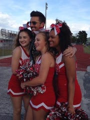 Vero Beach High School cheerleaders Gracie Welton, Lauren Paluzzi and Gabi McFall pose for photos with country music star Jake Owen.