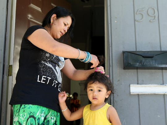 Bishal Mongar, the two year -old daughter of Jit Mongar who was killed on Lake Avenue Sunday night has her hair braided by Mongar's sister, Devi Gurung, on the porch of the family home. Jit had six other children, all under the age of 18, with his wife.
