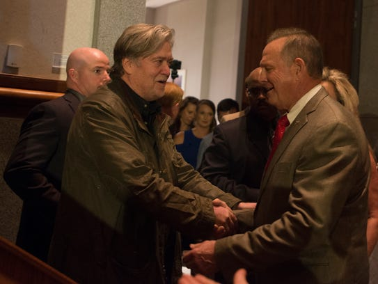 Roy Moore shakes the hand of Steve Bannon before giving