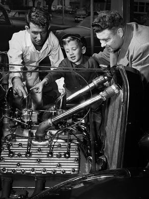 The Memphis Rodders Club exhibit of hot rods on display on March 15, 1952, at Klyce Motors at 17 South Cleveland has the air blue with technical terms. Here Jimmy Fulghum (left) explains that since his own hot rod has two carburetors, he has removed the choke butterflies in order to get more air through. Spectators are S.G. Sullivan, instructor at the Naval Air Technical Training Station at Millington, and his 5-year-old son John.