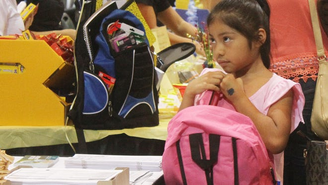 Kimberly Aguilar, 7, grasps her new backpack as she browses the isles for school supplies during last year's Big Backpack Event at the Harborside Event Center in Fort Myers. This year's event is scheduled for July 31.