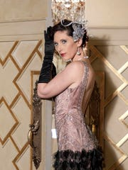 The director of The Product of The 20's Fashion Show, Sarah Merrell, wears a vintage beaded gown provided by Enchanted Forest, jewelry by Amber Hatchett Designs, and hair piece by Chapeaux by Simone.