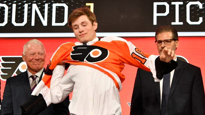 Joel Farabee puts on a Flyers jersey after being selected as the No. 14 overall pick Friday night.