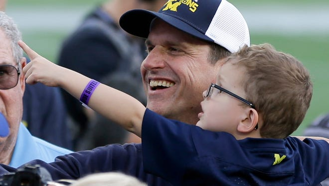 Michigan head coach Jim Harbaugh, left, holding his son Jack, celebrates after their 41-7 win over Florida in the Citrus Bowl NCAA college football game, Friday, Jan. 1, 2016, in Orlando, Fla. (AP Photo/John Raoux)