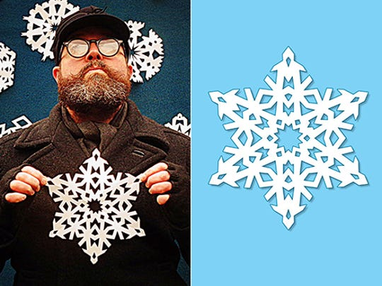 Artist Kipp Normand holds his snowflake