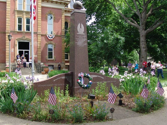 Onlookers stand in silence in the foreground of the Coshocton County War Memorial during the 2016 Memorial Day ceremony at the court square.