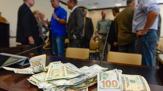 Supporters of San Juan County Commissioner Phil Lyman place money on the table following a meeting by members of Utah's Constitutional Defense Council at the Capitol on Wednesday, June 24, 2015, in Salt Lake City. State and local officials sympathetic to Lyman used their own dollars to pay legal bills involving his conviction in an ATV ride on a closed road to protest federal control of public lands. The county's sheriff is the latest elected official to become caught in a legal controversy, following criminal charges claiming he pointed a firearm at another officer during a shooting range incident.