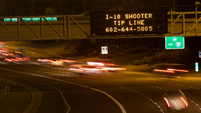 A sign displays a shooter tip hotline above Interstate 10  in Phoenix on Thursday, Sept. 10, 2015.   Authorities on Friday were questioning two people in a string of freeway shootings over the past two weeks that have rattled Phoenix and led to a massive search for suspects.