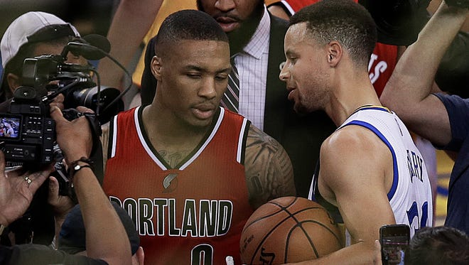 Golden State Warriors' Stephen Curry, right, speaks with Portland Trail Blazers' Damian Lillard at the end of Game 5 of a second-round NBA basketball playoff series Wednesday, May 11, 2016, in Oakland, Calif. The Warriors won 125-121 and advanced to the conference finals.