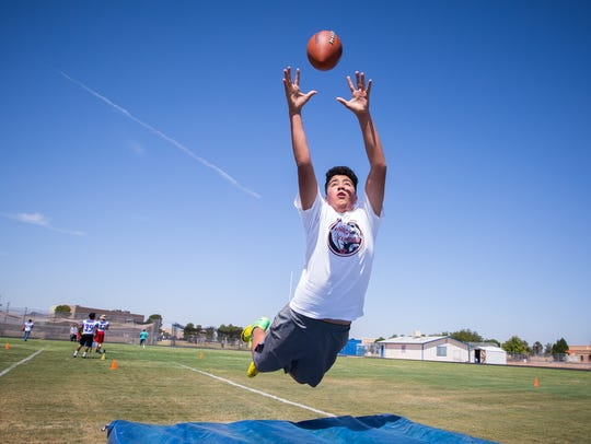13-year-old Jorge Figueroa leaps into the air to catch
