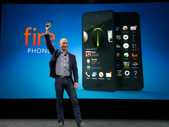 Amazon CEO Jeff Bezos holds up the new Amazon Fire