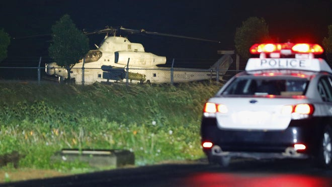 U.S. Marine Corps AH-1 attack helicopter sits near a Japanese police vehicle in Yomitan village, Okinawa, Japan, Monday, Jan. 8, 2018. The U.S. military helicopter with two people aboard made an emergency landing in a field at a waste disposal site on Okinawa islands in the second such incident in three days. No injuries were reported.