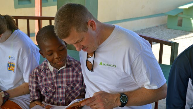 James Dusenberry reads with Jobenson Charles, a child who lives at the orphanage Dusenberry's church founded in Williamson, Haiti.