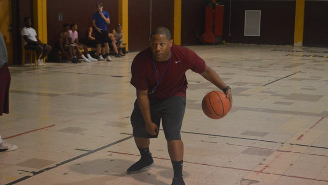 Grant coach Kendrick Moore goes over dribbling drills with his team in practice Thursday. Moore is the new boys basketball coach for the Cougars.
