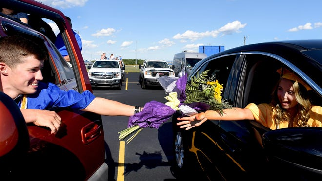 Hunter Assenmacher reaches out of his truck to to give flowers to his sweetheart, Julia Hogston, during their drive-thru graduation from Ida High School on July 29.