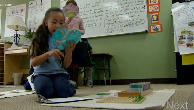 A student from Montessori del Mundo in Aurora reads the kind message to a stranger she wrote on her card as part of her class participating in the Care for Three project.