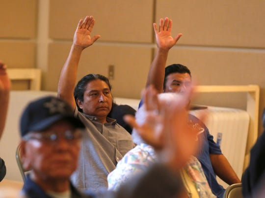At center, Gary Mike and fellow San Juan Chapter residents vote on a resolution, Tuesday during a special meeting at the San Juan Chapter House in Lower Fruitland.