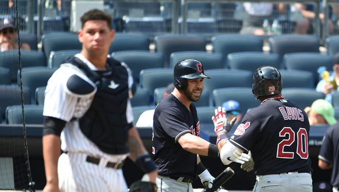 New York Yankees catcher Gary Sanchez, left, looks to the field as Cleveland Indians Jason Kipnis, center, greets teammate Rajai Davis, right, at home plate after Davis hit a solo home run off of Yankees relief pitcher Anthony Swarzak in the seventh inning of a baseball game, Saturday, Aug. 6, 2016, in New York. Kipnis also it a solo home run during the Indians 5-2 win.
