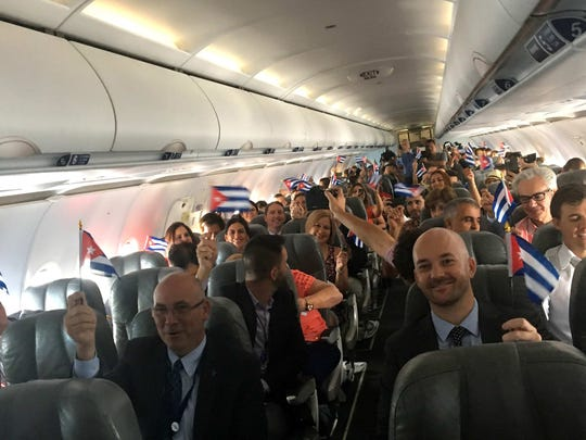 JetBlue flight 387 passengers hold up representations of Cuba's national flag, just before touching down at the airport in Santa Clara, Cuba, Wednesday, Aug. 31, 2016. JetBlue 387, the first commercial flight between the U.S. and Cuba in more than a half century, landed in the central city of Santa Clara on Wednesday morning, re-establishing regular air service severed at the height of the Cold War.