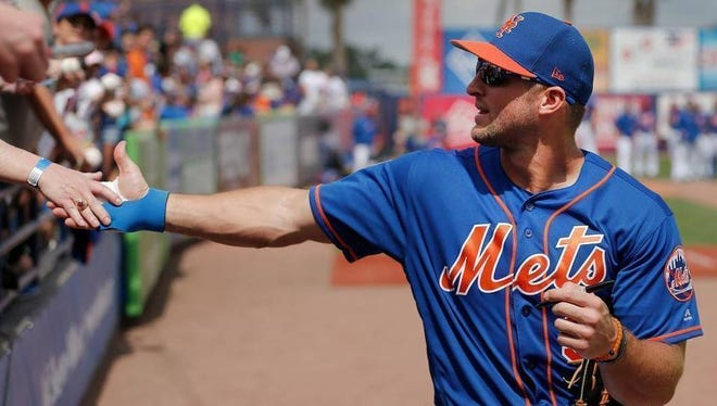 A fan reaches out to grab New York Mets' Tim Tebow's hand before a spring training baseball game.