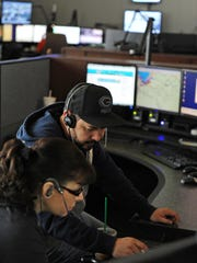 Dispatchers Sergio Ramirez and Lisa Perez work out a solution at Monterey County Emergency Communications in Salinas.