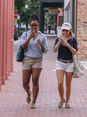 Miyah Jones, 20, and Lauren Caudill, 21, make their way up Palafox Place while playing Pokémon Go Sunday afternoon.