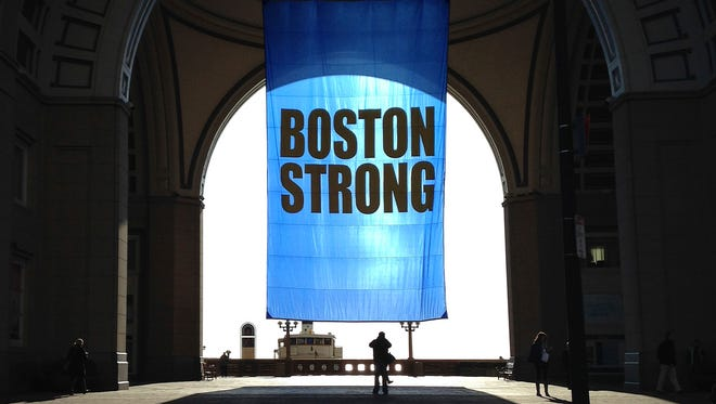People stop to photograph a Boston Strong banner hanging at Rowes Wharf in Boston.