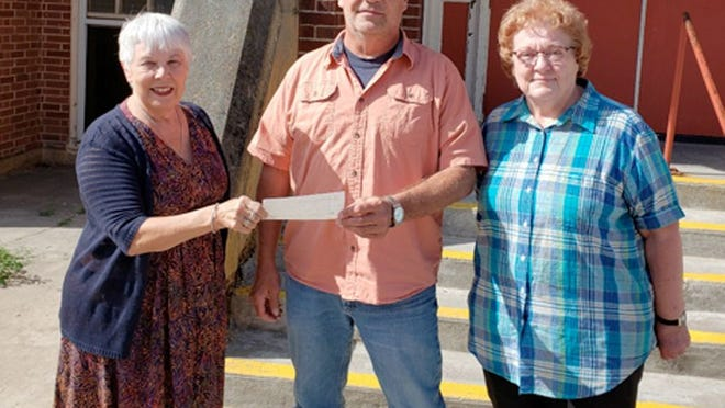 Pictured are Associates Gaye Wick (left) and Mary Normandin (right) presenting the check to Brian Halos, Care and Share executive director.