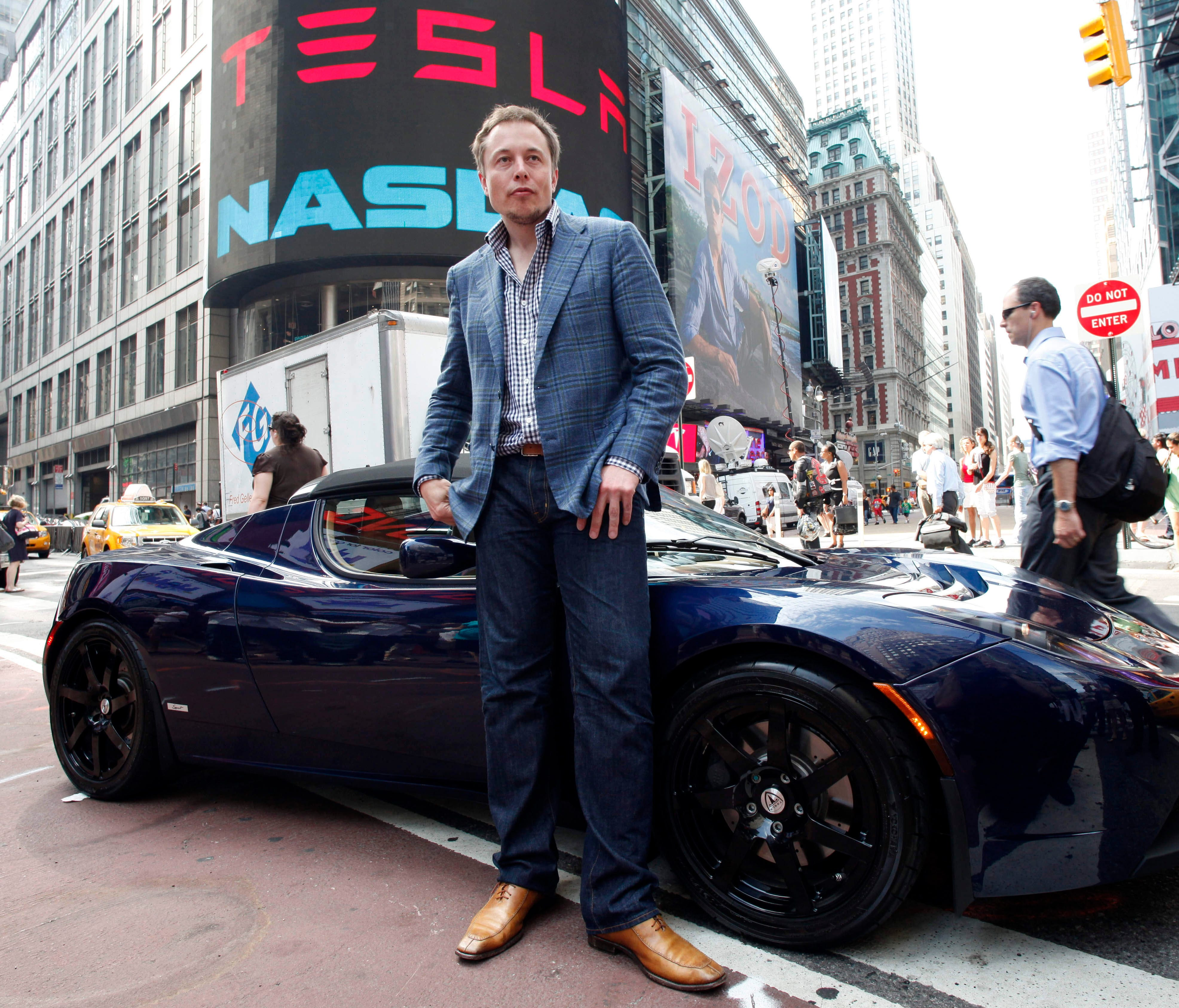 Elon Musk, CEO of Tesla Motors, poses with a Tesla car in front of Nasdaq following the electric automakerís initial public offering on June, 29, 2010, in New York.