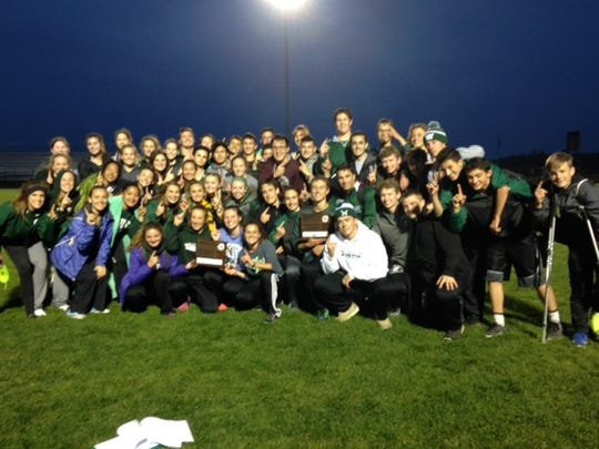 The Williamston boys and girls track teams pose for a picture Wednesday night after adding on to their league title streaks.