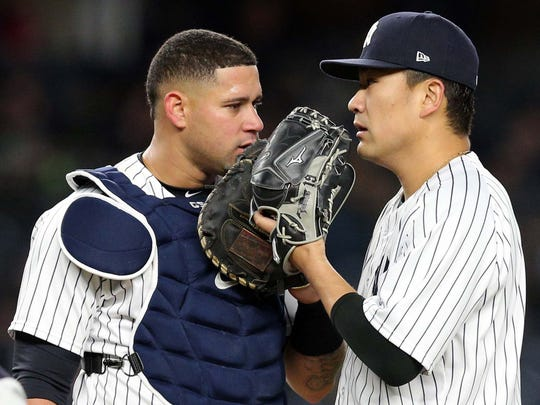 New York Yankees starting pitcher Masahiro Tanaka (19) talks to catcher Gary Sanchez (24) during the fifth inning against the Miami Marlins at Yankee Stadium.