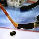 Hockey players go after a puck.