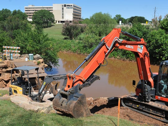 Heavy construction equipment is used to remove concrete near the Circle Trail bridge that crosses the falls near Lucy Park. The trail near the bridge will be closed while contractors work to remove the wooden structure and replace it with a wider, sturdier bridge.